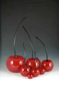 7 red glass cherries with black stems