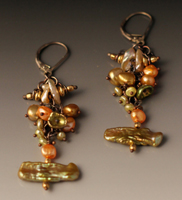 earring of dangling pearls of different sizes, colors and shapes.