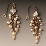 dangling earrings of all white pearls of different sizes.