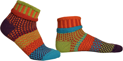 Mismatched socks with lots of orange, some turquoise, some light green, some yellow.